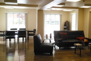 sitting area with couch and chairs, table area with chairs, large windows with light
