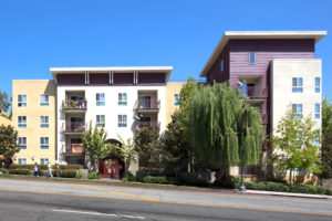Exterior shot from street with balconies, trees, and people walking on sidewalk
