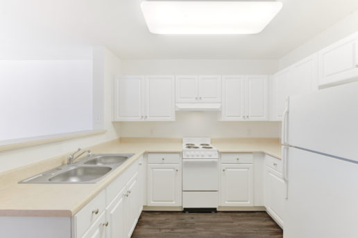 bright kitchen with wood floors and white cabinets