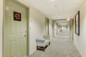 carpeted hallway with green doors